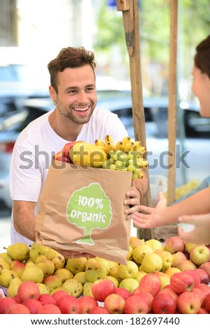 Greengrocer owner of a small business selling fruits and vegetables to a woman carrying a shopping paper bag with a 100% organic certified label. - stock photo