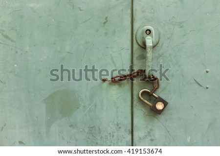 Greenish door with rusty chain and lock.