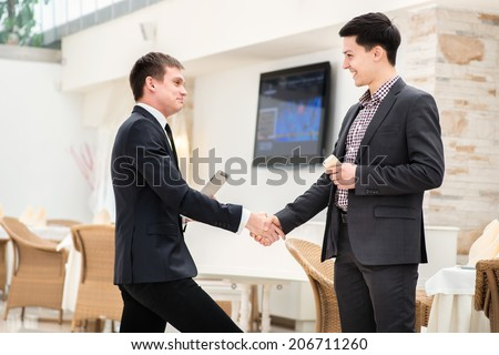 Greeting at work. Two successful and confident businessman standing in office and shake hands - stock photo