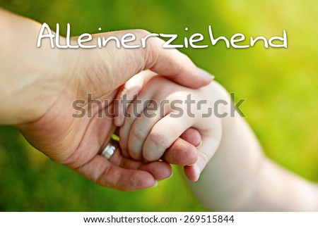 greeting card background - hands of mother and child - german for single parent - stock photo