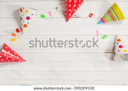 Greeting card for carnival party. Party hat and candles on wooden background. Toning instagram filter. - stock photo