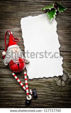 Greeting card for Christmas with Santa Claus decoration and holly - stock photo
