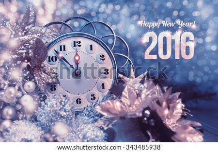 """Greeting card """"Happy New Year 2016!"""" with vintage clock showing five to mignight and sparkling lights. This image is toned. Shallow DOF, focus on the clock arms and numbers - stock photo"""