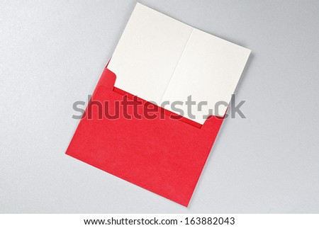 Greeting card in red envelope over gray background