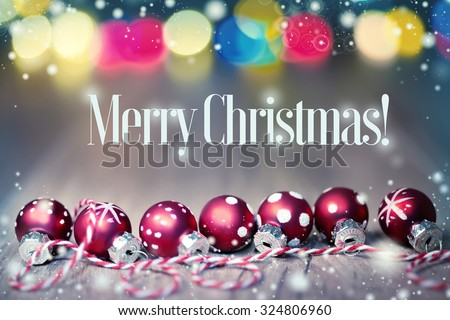 """Greeting card """"Merry Chistmas!"""" with red baubles on checkered coard and festive lights - stock photo"""