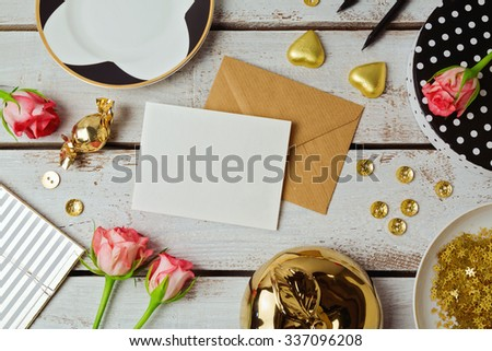 Greeting card mock up template with rose flowers and chocolates on wooden background. View from above - stock photo