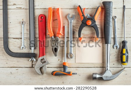 Greeting Card to Happy Father's Day, concept, set of different tools: a hammer, Hand saw, pliers, wrench, screwdriver, various spanners, clamp and tablet for an inscription, text, closeup, top view - stock photo
