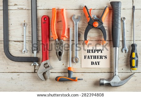 Greeting Card to Happy Father's Day, concept, set of different tools: a hammer, Hand saw, pliers, wrench, screwdriver, various spanners, clamp on a wooden background and text , closeup, top view - stock photo