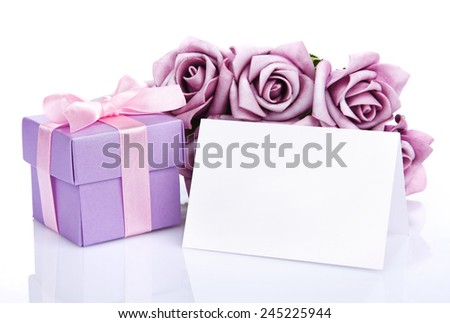 Greeting card with purple flowers and gift box with ribbon and bow on a white background - stock photo