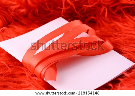 Greeting card with white paper and red bow - stock photo