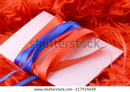 Greeting card with white paper with blue and red bow - stock photo