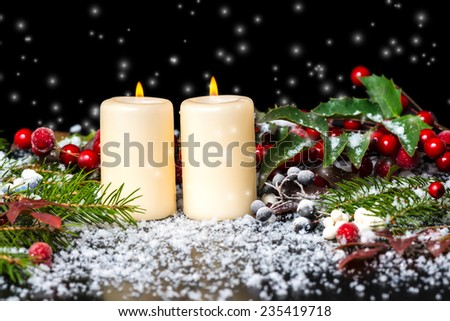 Greeting Christmas card of decorated evergreen branches, red leaves, berry with snow and candles, closeup - stock photo