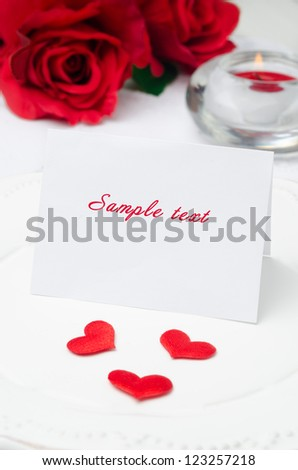 greeting Valentine's Day card on a plate, roses and candle