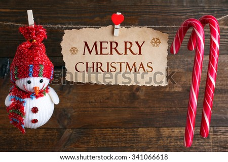 greetings merry Christmas written on the paper and Christmas decorations with candy on a rope on a wooden brown background - stock photo