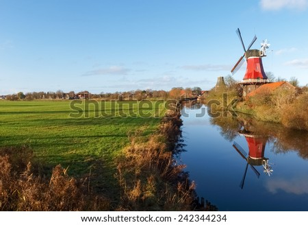 Greetsiel, Germany: Traditional Windmill working and still used to grind. The second mill is currently under renovation due to a violent hurricane. - stock photo