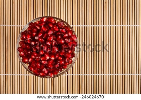 Grenadine seeds in a glass bowl on wooden sticks - stock photo