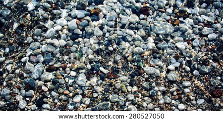 Grey and black pebbles on the riverbed. Aged photo. Smooth stones under water. Toned effect. Sunlight on the water surface. Vintage effect image. Cirali, Antalya Province, Turkey. - stock photo