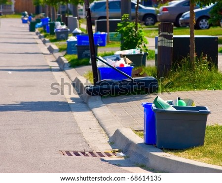 Grey and blue recycling bins by the curb on a residential street. - stock photo