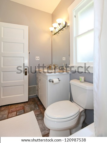 GREY and white small bathroom with open door.