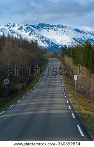 Grey asphalt road in Norvegian green mountains - stock photo