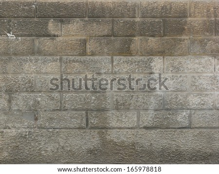 Grey brick wall with rough texture and soft hints of beige. - stock photo