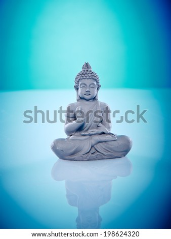 Grey buddah isolated on blue background Wellness and Spa Image, works perfect for advertising Health and Beauty, Spirituality or Massage. - stock photo