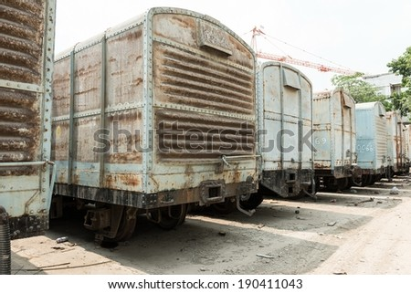 Grey cargo train carriage in train yard, taken on a sunny day