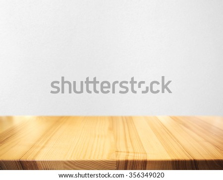 Grey cement wall and wooden desk - stock photo