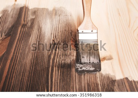 Grey color painting on wooden table or fence or wall, or flour, use for home decorated. House renovation. Half - painted surface. Smear of paint brush. - stock photo