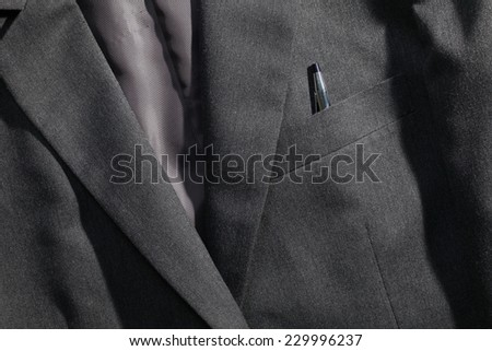 Grey color suit represent the formal uniform for businessman in the scene appear chrome ball pen strongly reflection shiny bright light also.