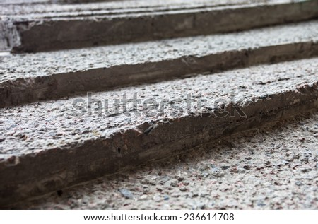 Grey concrete stairs with rough textured surface.