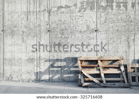 Grey concrete wall with wood palette. Construction site. Sunset.