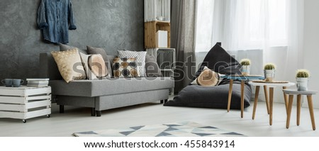 Grey corner of a modern apartment, with a comfy sofa and a sitting sack with pillows imitating wood trunks
