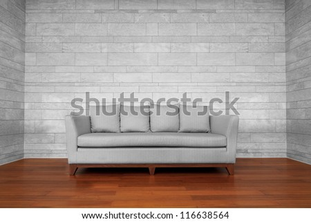 Grey couch chair on brown wooden floor and white wall - stock photo