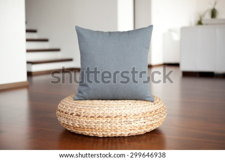 Grey decorative pillow in white interior on wood pouffe - stock photo