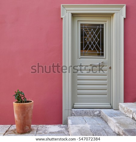 grey door on colorful fuchsia house wall and a flowerpot
