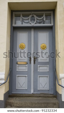 Grey double door with golden decoration. Shot from a street in Viborg, Denmark