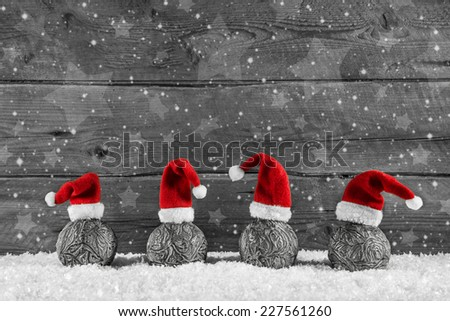 Grey festive wooden christmas background with four santa hats on balls. - stock photo