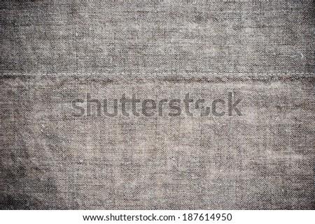 Grey flax napkin background with a stitch - stock photo
