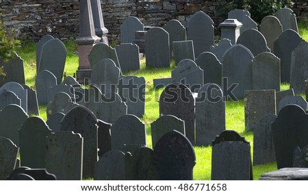 Grey gravestones backlight in graveyard