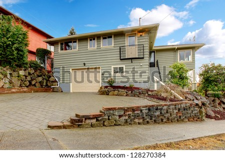 Grey green newly remodeled two level house exterior with beige trim. - stock photo