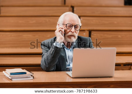 grey hair professor talking by smartphone and looking at laptop