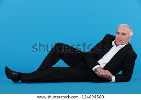 Grey-haired businessman laying on the floor