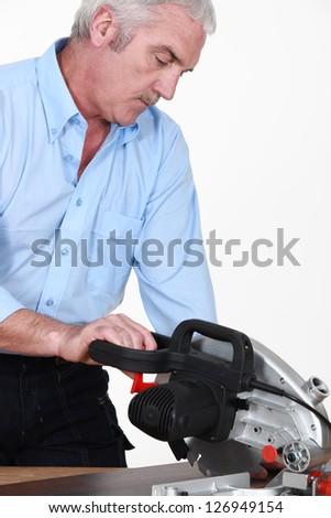 Grey-haired carpenter sawing laminate flooring - stock photo