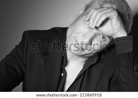 Grey-haired man in a suit at the age of forty-six years old hand covers one eye looking at the camera on the background of a rough wall with texture - stock photo