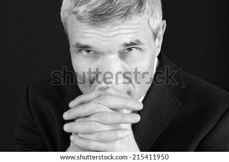 Grey-haired man in suit at the age of forty-six years old  with hands to head support  looking at the camera on black background - stock photo