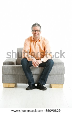 Grey haired man wearing jeans and orange shirt sitting on couch, talking on mobile phone. Isolated on white.?