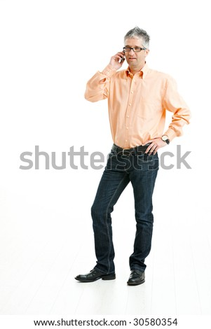 Grey haired man wearing jeans and orange shirt standing and talking on mobile phone. Isolated on white.