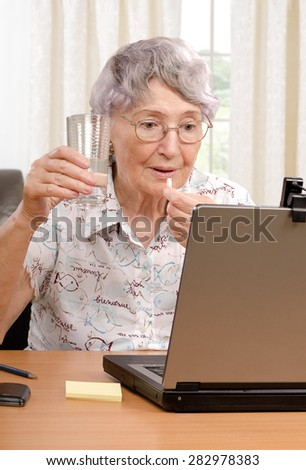 Grey haired old woman is taking pill during unpleasant on-line conversation on the Internet. Vertical shot