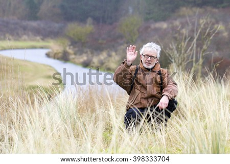 Grey Haired Older Man with Glasses and Brown Leather Jacket Sitting in a Nature Background Waving to the Camera - stock photo